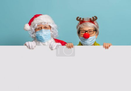 Merry Christmas and Happy Holidays! Santa Claus and reindeer on bright color background. Senior people in carnival costumes wearing face masks during Covid-2019