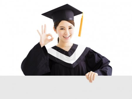 Happy female graduate showing blank board with ok gesture