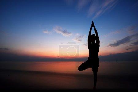 在日落时分剪影与专业的瑜伽姿势在海滩上的一名女子图片