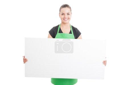 绿色的围裙,拿着空白广告牌的开朗雇员