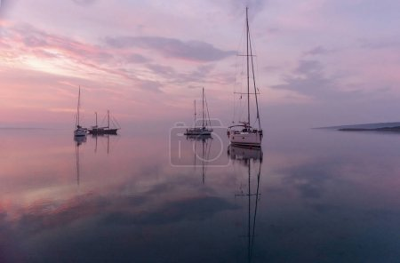 Moored sailboat early in the morning in the bay before sunrise