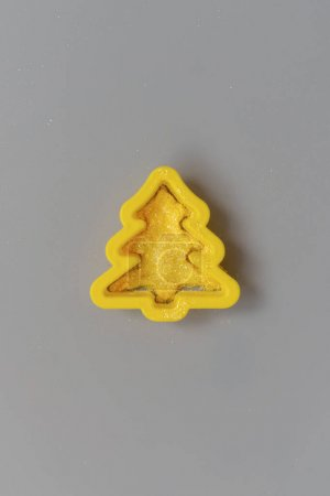 Christmas tree yellow plastic cutter on gray.