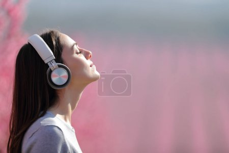 Profile of a woman meditating listening audio on wireless headphones in a pink field