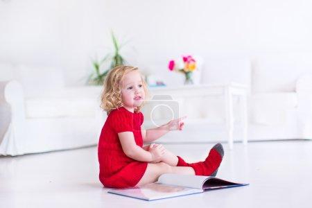 可爱的小女孩,穿着一件温暖的针织红裙子和袜子读一本书,坐在一个