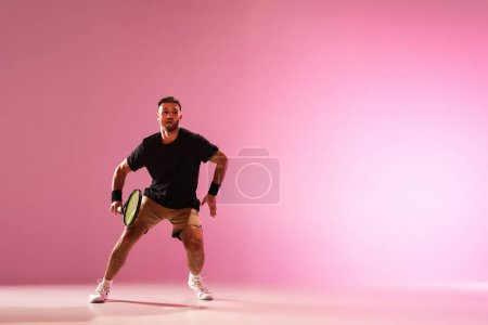 Young caucasian man playing tennis isolated on pink studio background, action and motion concept
