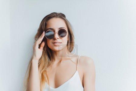 Young girl posing on sunglasses