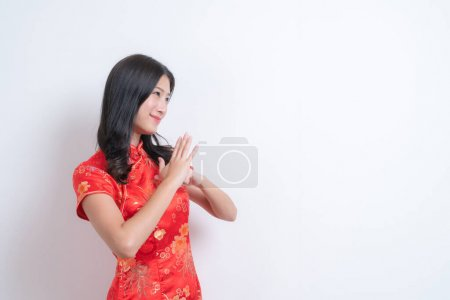 beautiful and young asian woman wear red chinese traditional dress and smiling for Chinese New Year on white background